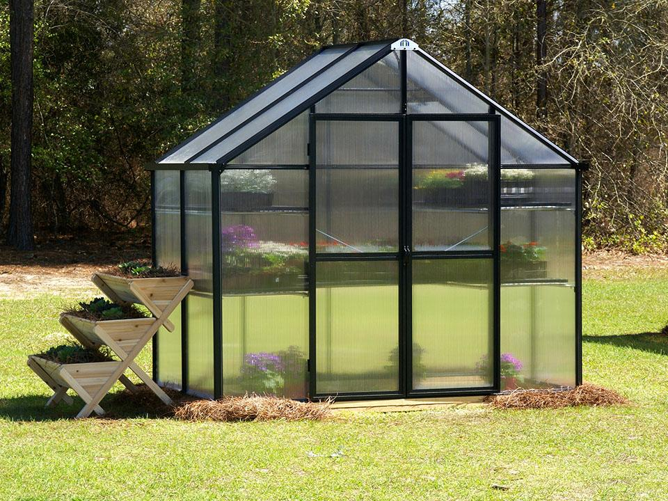 Eden Waterfall Garden Table next to small Patio Greenhouse from Riverstone Industries