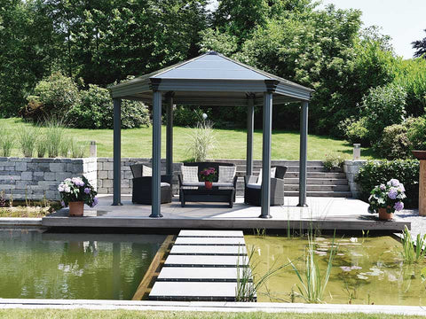 Image of Roma Garden Gazebo in a garden by the pond with a living room set up