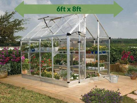 Image of Palram 6ft x 8ft Snap & Grow Hobby Greenhouse - HG6008 - full view - green arrow on top - in a garden