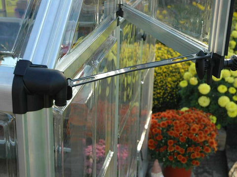 Image of Close up of the Palram 6ft x 16ft Snap & Grow Hobby Greenhouse with flowers for Palram Hobby Greenhouses