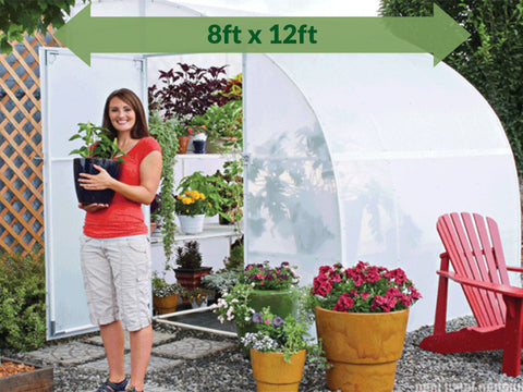 Image of Solexx  8ft x 12ft Harvester Greenhouse G-412 - full view - open doors - green arrow on top showing dimensions - a woman carrying a pot