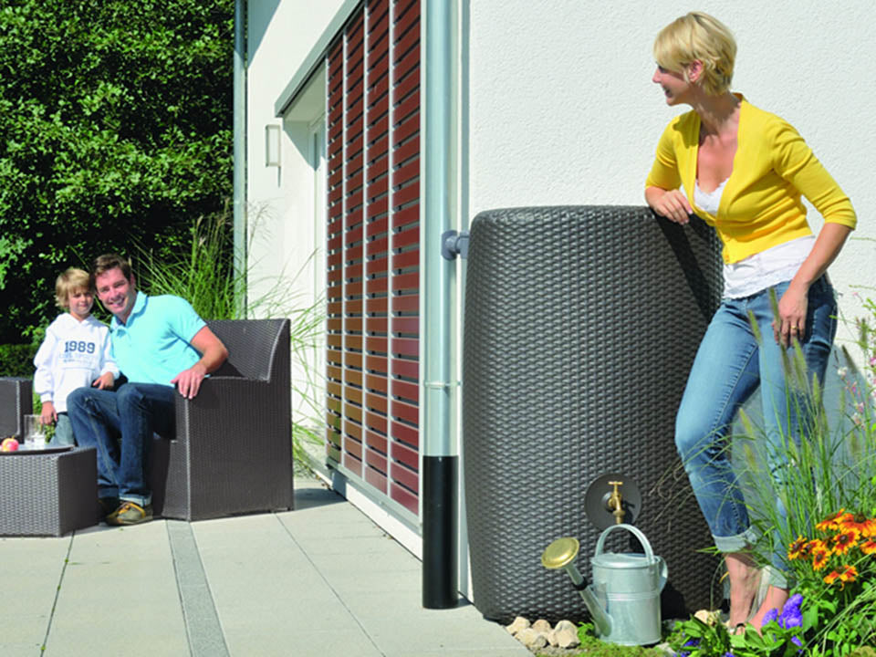 Dark brown Sunda Wicker Look Rain Barrel outdoor with a woman on the right side leaning toward it
