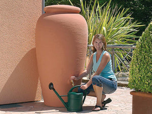 A woman on the right side pouring water from the Venetia Rain Barrel with Planter
