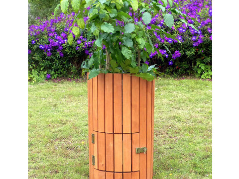 Closed side door of Wooden Potato Planter in a garden with plant on top