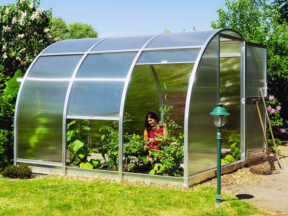 Open doors and sides of Arcus greenhouse with a woman gardening inside