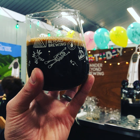 Hand holding a glass of dark beer with multicoloured balloons in the background.
