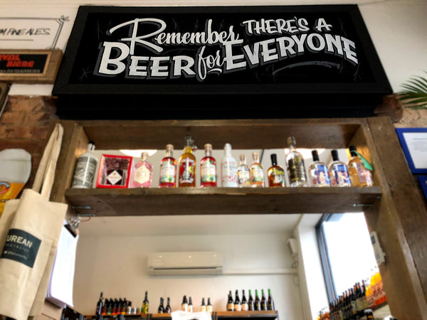 Photograph showing a hand-written chalk sign that reads 'Remember, there's a beer for everyone'.