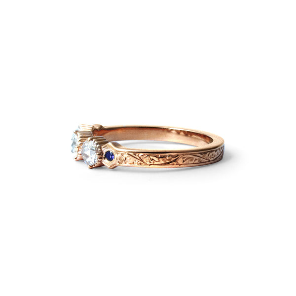 Crafted in 14KT rose gold, this ring features 3 round brilliant-cut diamonds in a row, with a blue sapphire on either side on a vintage-inspired hand engraved band.