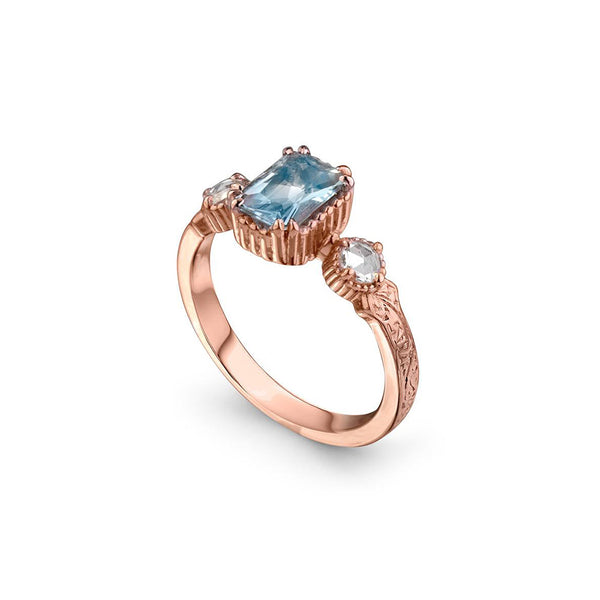 Crafted in 14KT rose gold, this ring features an aquamarine between two round brilliant-cut diamonds on a vintage-inspired hand engraved band.