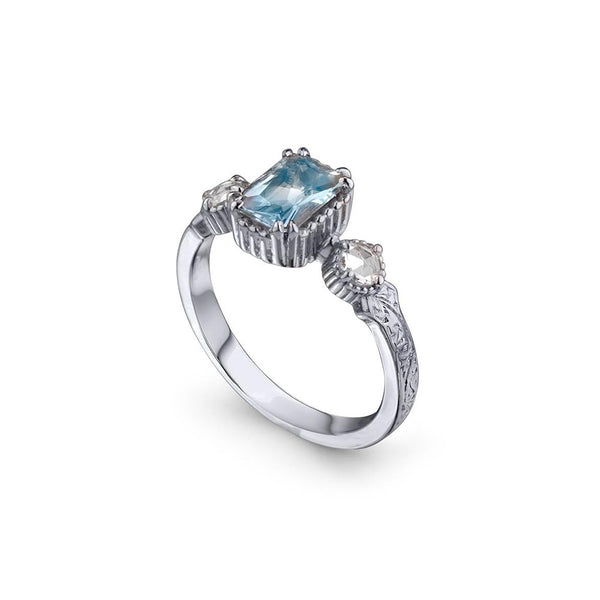 Crafted in 14KT white gold, this ring features an aquamarine between two round brilliant-cut diamonds on a vintage-inspired hand engraved band.