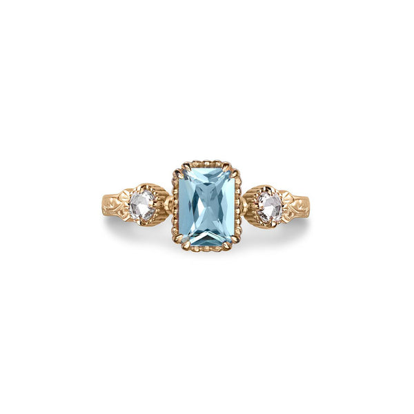 Crafted in 14KT yellow gold, this ring features an aquamarine between two round brilliant-cut diamonds on a vintage-inspired hand engraved band.