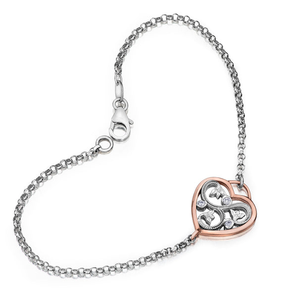 Bracelet crafted in 14kt white Canadian Certified Gold featuring rosebud vines embracing a round brilliant-cut Canadian diamond and two smaller diamonds, all set within a lovely rose gold heart on a rolo chain.