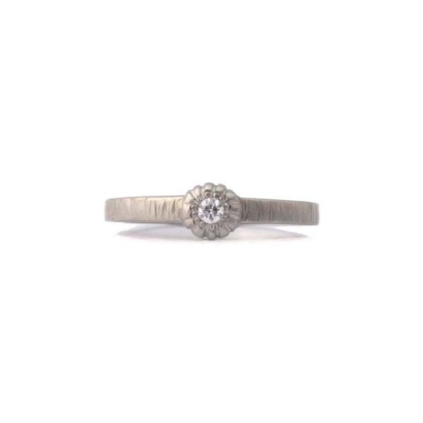 Crafted in 14KT brushed white gold, this classic ring is set with a round brilliant-cut diamond.