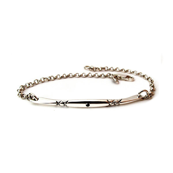 Crafted in 14KT yellow gold, this bracelet has a bar set with a black diamond and x-designs.