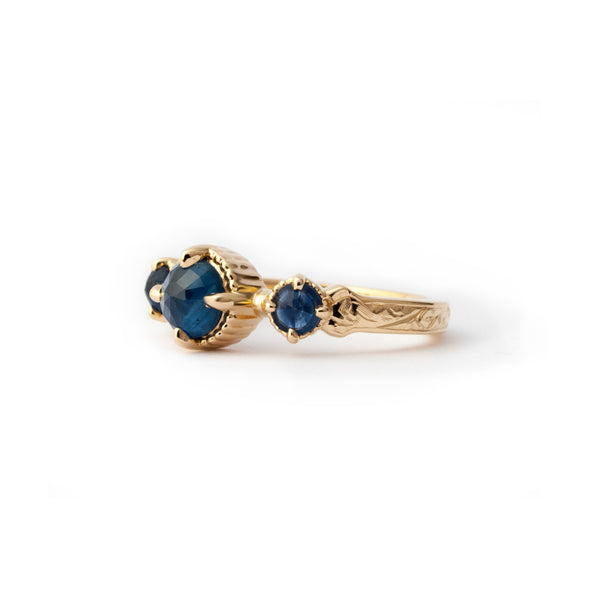 Crafted in 14KT yellow gold, this ring features a blue sapphire set between two smaller ones on a vintage-inspired hand engraved band.