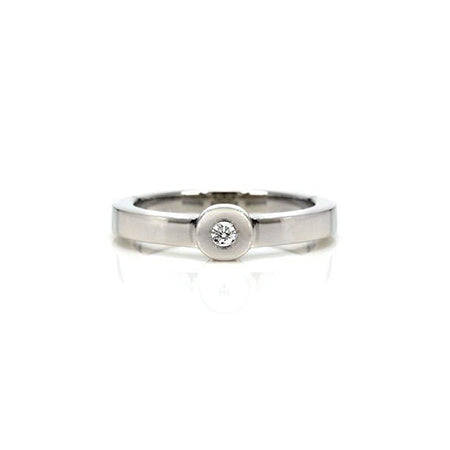 Crafted in 14KT white gold, this ring features a bezel set round brilliant-cut diamond and a flat band.