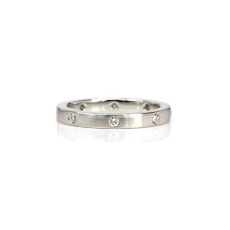 Crafted in 14KT white gold, this ring features eight round brilliant-cut diamonds evenly spaced apart on a flat band.