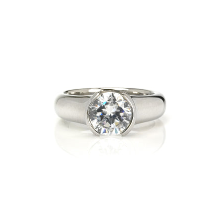 Crafted in 14KT white gold, this ring features a round-cut diamond in a half-bezel setting.