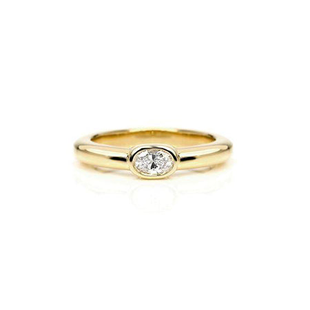 Crafted in 14KT yellow gold, this ring features a bezel set oval-cut diamond.