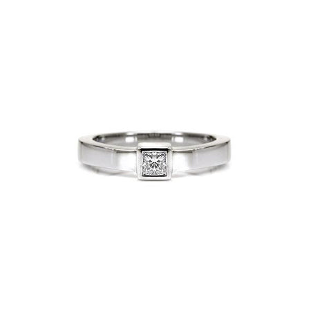 Crafted in 14KT white gold, this ring features a bezel set princess-cut diamond and a flat band.