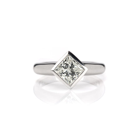 Crafted in 14KT white gold, this ring features a bezel set princess-cut diamond.
