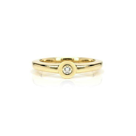 Crafted in 14KT yellow gold, this ring features a bezel set round brilliant-cut diamond with a flat halo.