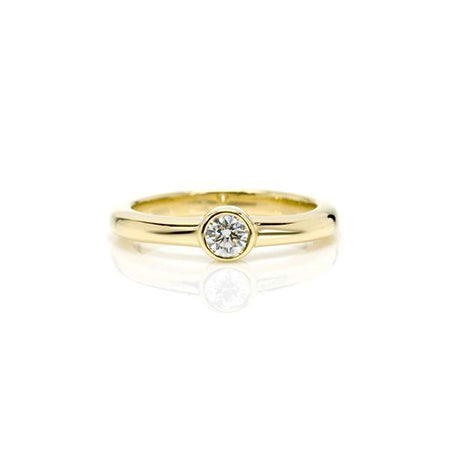 Crafted in 14KT yellow gold, this ring features a bezel set round brilliant-cut diamond.