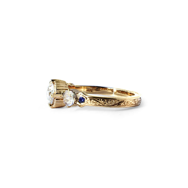 Crafted in 14KT yellow gold, this ring features a large rose-cut diamond with a smaller diamond and a blue sapphire on each side. All on a vintage-inspired hand engraved band.