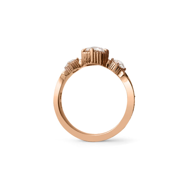 Crafted in 14KT rose gold, this ring features a large rose-cut diamond with a smaller diamond and a blue sapphire on each side. All on a vintage-inspired hand engraved band.