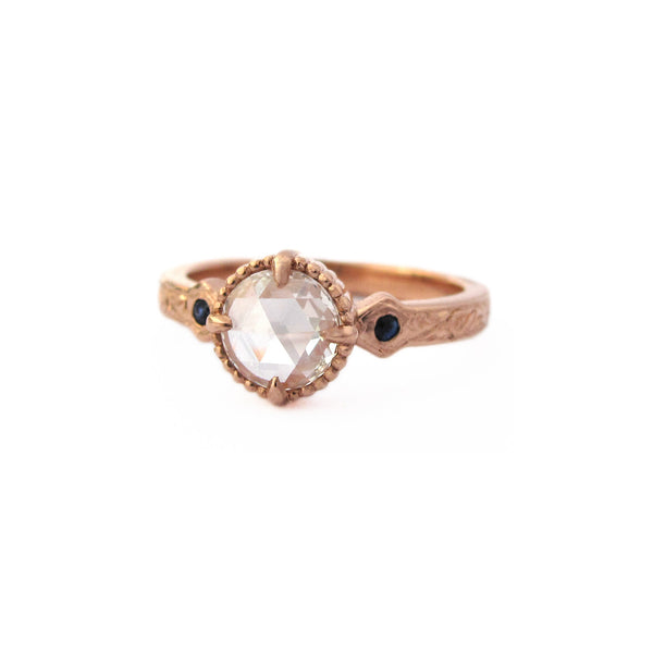 Crafted in 14KT rose gold, this ring features a large rose-cut diamond with two blue sapphires at its side on a vintage-inspired hand engraved band.