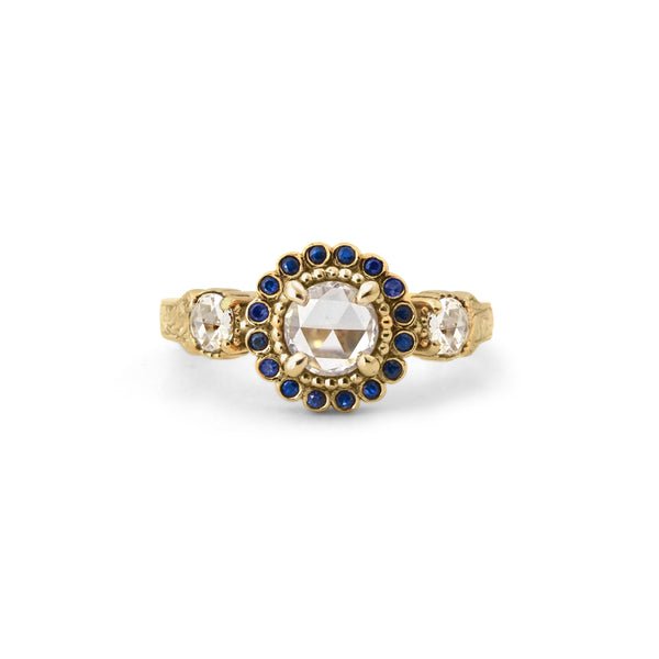 Crafted in 14KT yellow gold, this ring features a white rose-cut centre diamond with a blue sapphire halo and 2 smaller rose-cut diamonds on its sides.  All on a vintage-inspired hand engraved band.