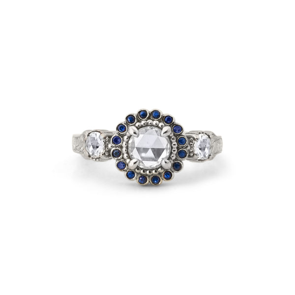 Crafted in 14KT white gold, this ring features a white rose-cut centre diamond with a blue sapphire halo and 2 smaller rose-cut diamonds on its sides.  All on a vintage-inspired hand engraved band.