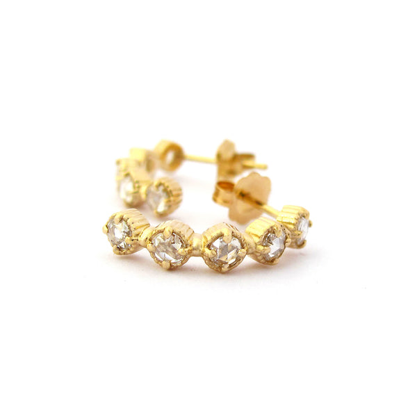 Crafted in 14KT yellow gold, these half-hoop earrings feature five rose-cut diamonds each in cupcake settings.