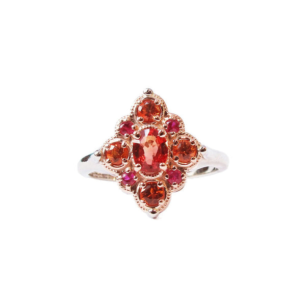 Crafted in 14KT rose and white gold, this ring features round and oval-cut orange and red sapphires set in a diamond shape.