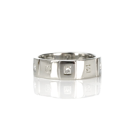 Crafted in 14KT white gold, this men's band features six raised sections, each set with a princess-cut diamond. Alternating with hand-engraved orange blossoms in square settings.