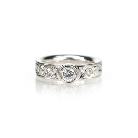 Crafted in 14KT white gold, this comfort-fit ring is set with a round brilliant-cut diamond between two smaller round brilliant-cut diamonds on a paisley hand-engraved band.