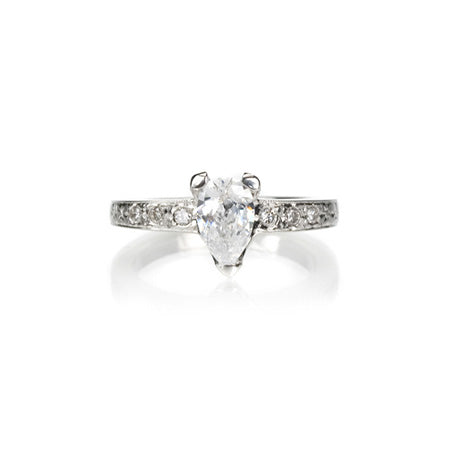 Crafted in 14KT white gold, this ring features a pear-shape diamond in a three prong setting on an orange blossom hand-engraved band set with round-cut  diamonds.