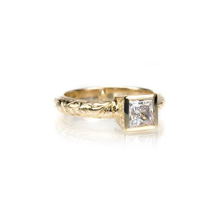 Crafted in 14KT yellow gold, this ring features a bezel set princess-cut diamond with accent diamonds on either side on a paisley hand-engraved band.