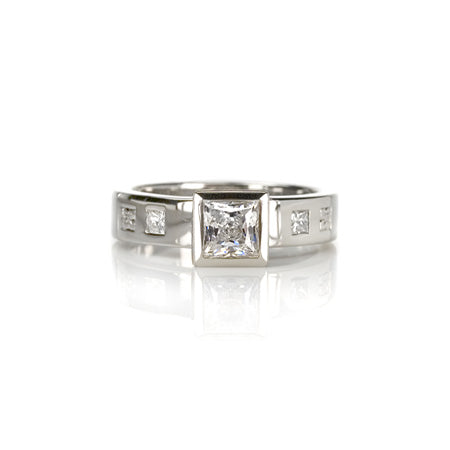 Crafted in 14KT white gold, this ring features a raised bezel set princess cut diamond. Band is set with princess-cut diamonds.