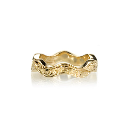 Crafted in 14KT yellow gold, this ring has a ruffled band with orange blossom hand-engravings.