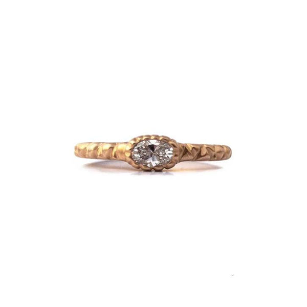 Crafted in 14KT brushed yellow gold, this ring is set with a oval-cut diamond and a quilted band.
