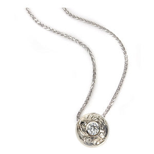 Crafted in 14KT white gold, this slider pendant features a round brilliant-cut diamond with a paisley hand-engraved halo.