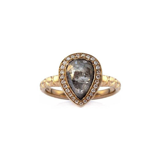 Crafted in 14KT yellow gold, this ring features a diamond halo with a grey pear-shape rose-cut diamond canter and a quilted band.