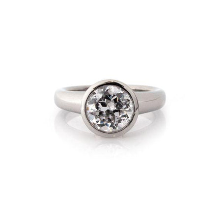 Crafted in 14KT white gold, this ring features a bezel set round-cut diamond with signature trademark on both sides.