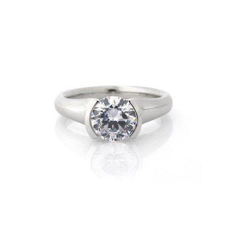 Crafted in 14KT white gold, this ring features a half-bezel set round brilliant-cut diamond with signature trademark on both sides.