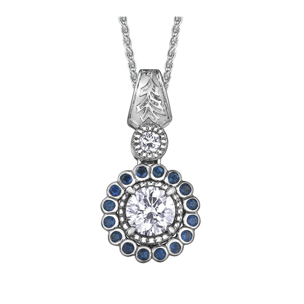 Crafted in 14KT white Canadian Certified Gold, this necklace features a regal blue sapphire halo with a round brilliant-cut Canadian centre diamond with a frost-inspired hand engraved bail.