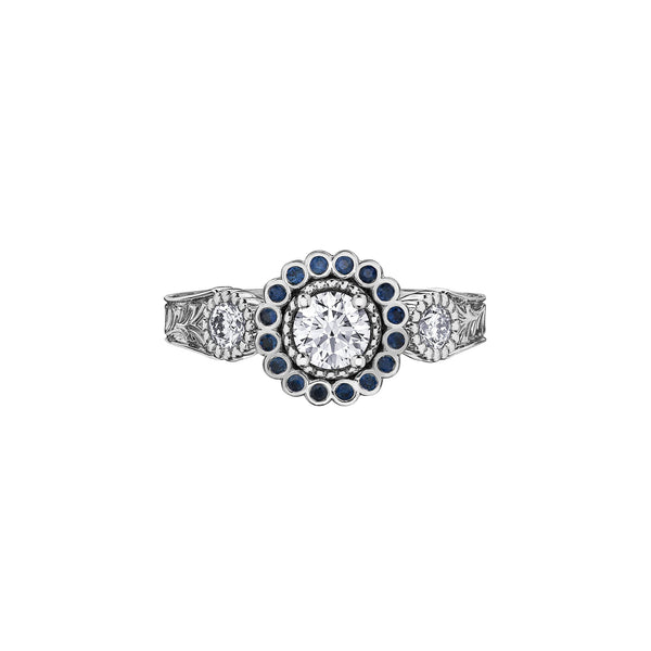 Crafted in 18KT white Canadian Certified Gold, this ring features a regal blue sapphire halo with a round brilliant-cut Canadian centre diamond on a frost-inspired hand engraved band.