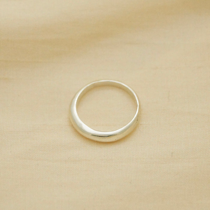 thin yet sturdy silver ring, bulbous and smooth, sitting on fabric