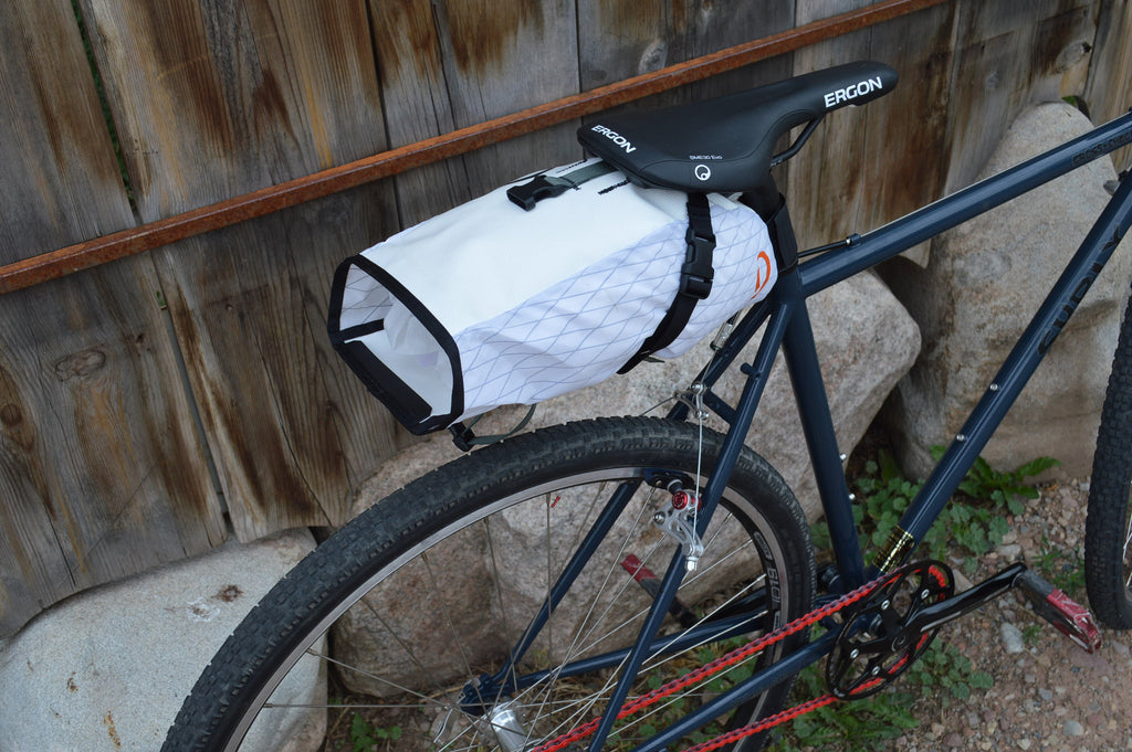 Rear-view of white/white Toklat Seat bag Medium on bike showing bag opening
