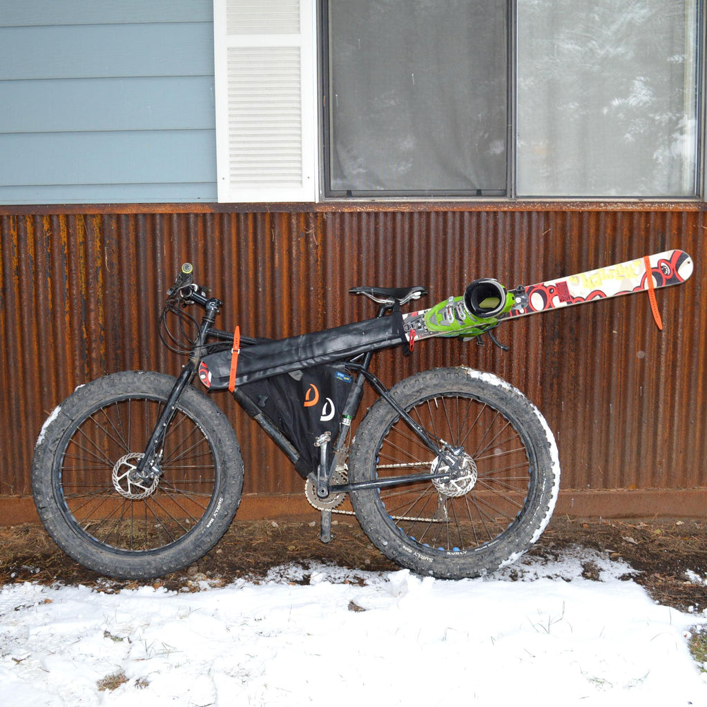 Bike with black custom framebag and Gunslinger Ski Carry with skis and boots attached
